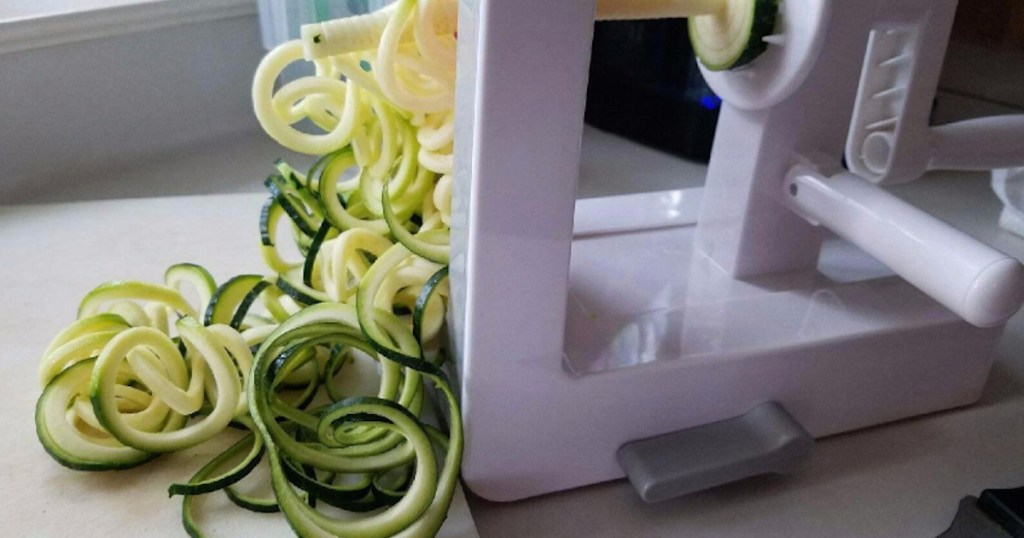 white food slicer on counter with sliced veggies zucchini
