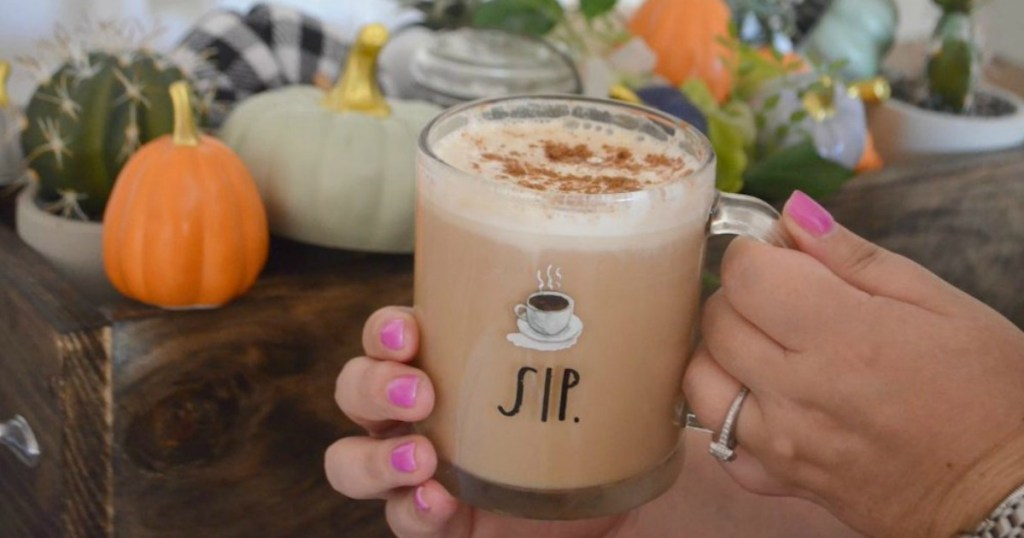 living Hygge lifestyle while holding latte with pumpkins and fall decor in the background