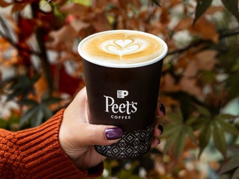 hand holding cup of coffee by fall leaves