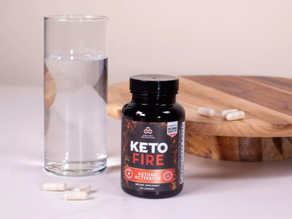 ketofire capsules next to a glass of water