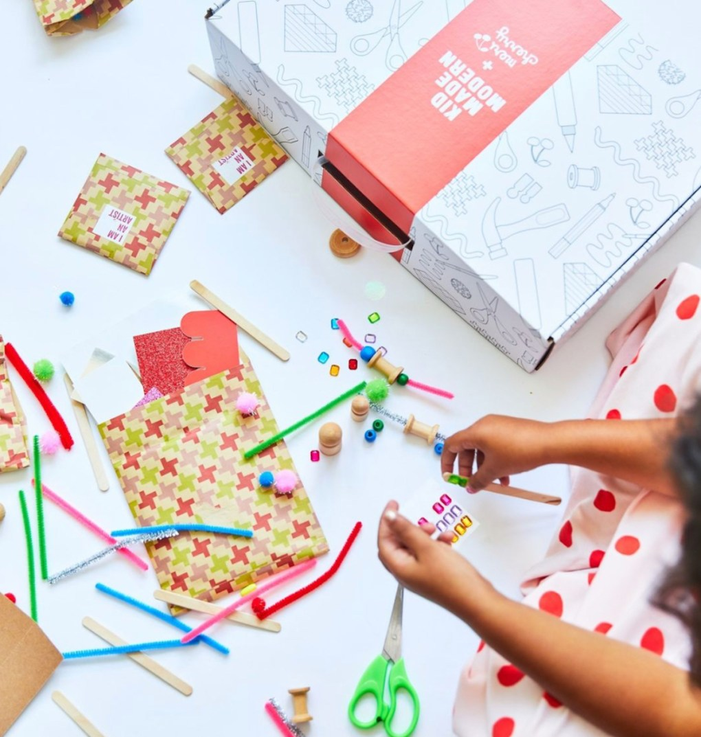 kid playing with craft supplies on white table