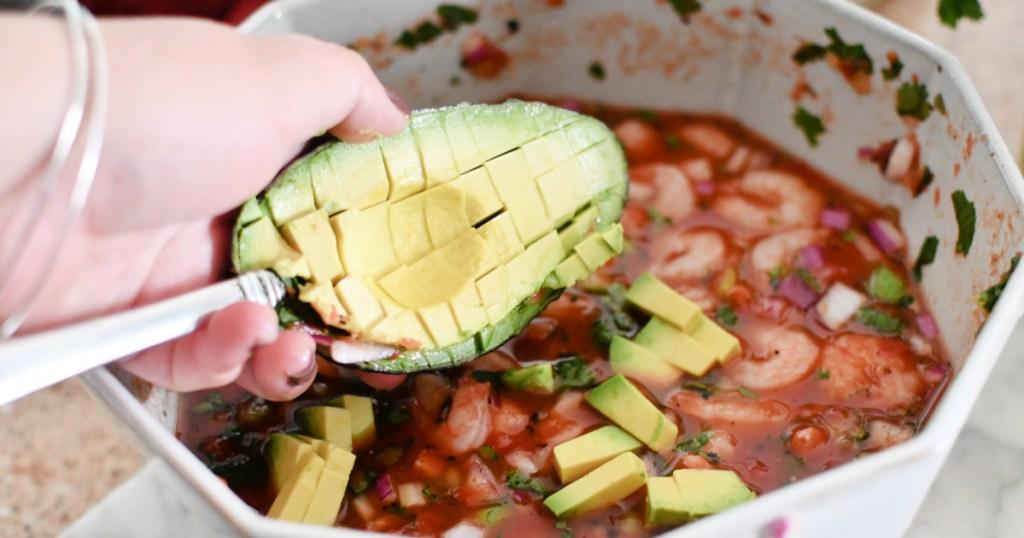 adding avocado to mexican shrimp cocktail