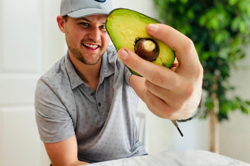 man holding half a cut avocado in hand