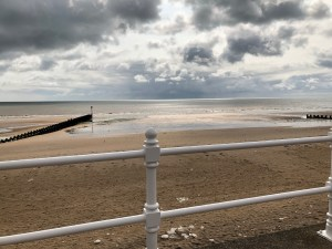 Slightly overcast beach shot from the promenade, sun glints through the clouds at Bridlington