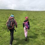 Hip2trek kids walk up steep hill with backpacks