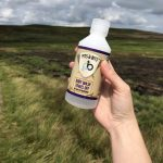 Pits and Bits bodywash being held up, moorland behind