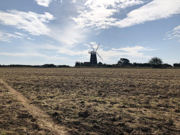 Windmill across a recently cut hay field