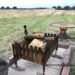 Firepit in foreground, hay bales and field can be seen in background