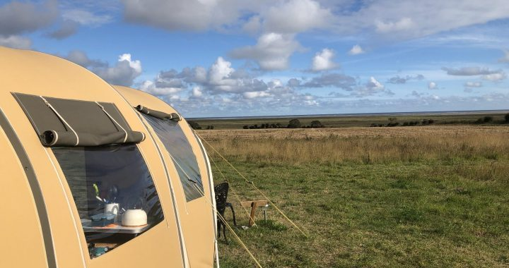 View of saltmarshes, tent in foreground