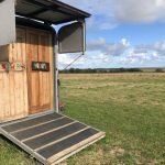 Converted horse box and countryside view behind