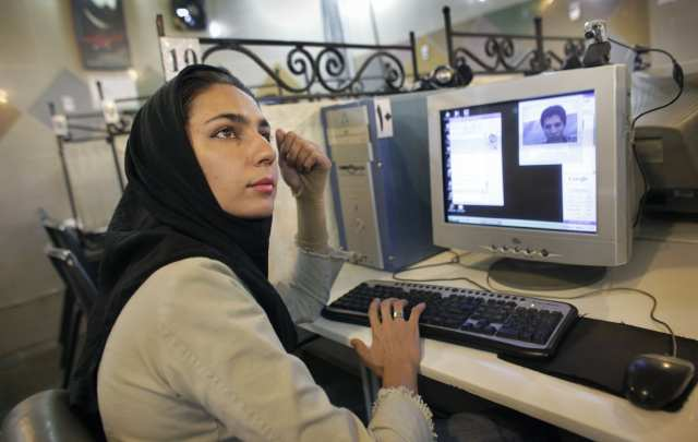 FILE - In this Thursday, June 11, 2009 file photo, an Iranian woman who declined to give her name uses the internet at an internet cafe in northern Tehran, Iran. Iranian authorities have slowed Internet connections to a crawl or choked them off completely before expected student protests Monday, to deny the opposition a vital means of communication. (AP Photo/Ben Curtis, File)