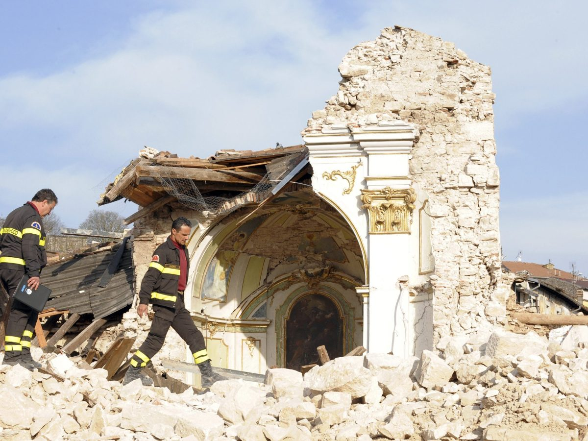 Fire department rescue personnel walk through the rubble of Saint Gregorio Magno church in Saint Gregorio village near L'Aquila April 12, 2009. Thousands of people made homeless by Italy's deadliest earthquake in 30 years celebrated a sombre Easter on Sunday, huddling for mass at makeshift chapels set up in tent cities and emergency shelters. REUTERS/Alessandro Bianchi (ITALY DISASTER RELIGION)