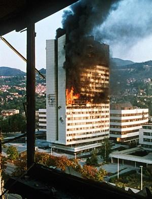 El edificio del parlamento bosnio en Sarajevo en llamas después de sufrir un ataque con fuego de artillería, 1992. <a href=