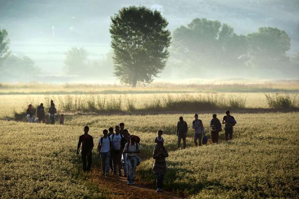 Refugiados sirios caminando en el campo cercano a la frontera entre Grecia y Macedonia. AFP - Aris Messinis.
