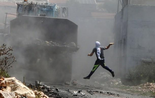 Un manifestante palestino lanza un cóctel-molotov contra un tanque israelí. AFP - Jaafar Ashtiyeth.