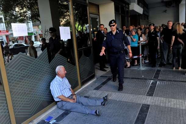 Un jubilado griego llora junto a un banco de Tesalónica tras el límite de retirada diaria de 120 euros. AFP - Sakis Mitroldis.