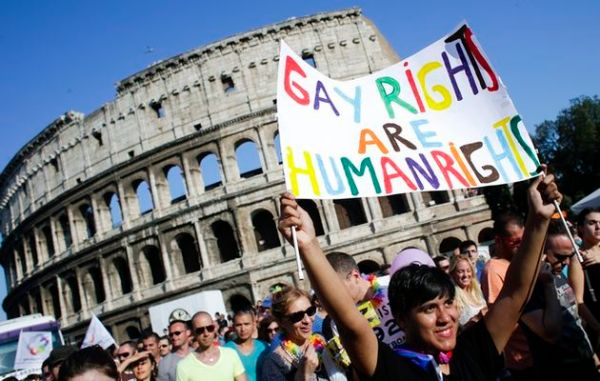A woman holds her banner in front of the Colosseum during the annual gay pride parade in downtown Rome