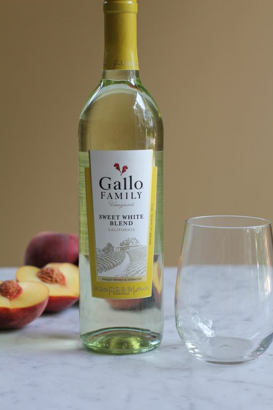 A bottle of white wine, an empty glass, and peaches.