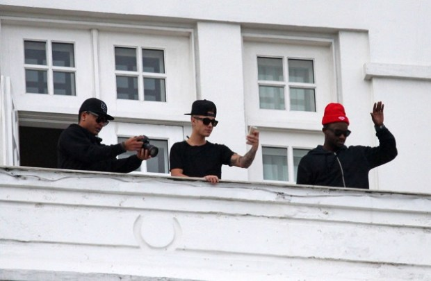 Justin Bieber films his many excited fans on his iPhone from the balcony of the Copacabana hotel in Rio de Janeiro
