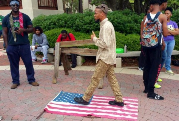 Eric Sheppard walking on an American flag during a protest.