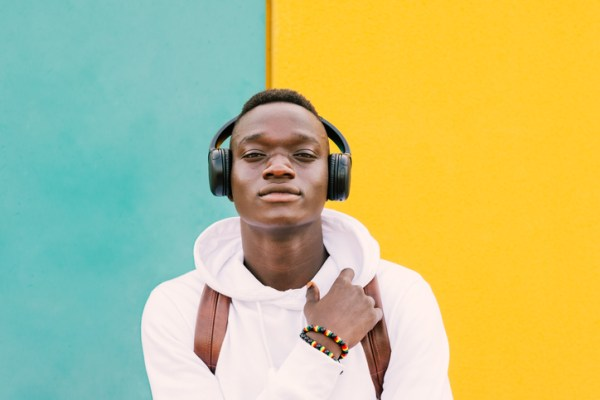 Portrait Of Young Man Standing Against Colored Wall