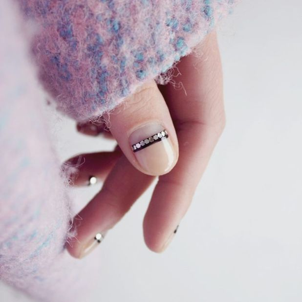 """<p>Nail ArtistFrédérique Olthuis gave her negative nail a subtle shine. To get the look, paint a clear base coat and let dry. Add a thin,black stripe at the half moon. When tacky, add metallic flat sequins to the strip and seal it with a clear top coat.</p><p><em data-redactor-tag=""""em"""" data-verified=""""redactor"""">Design by<span class=""""redactor-invisible-space"""" data-verified=""""redactor"""" data-redactor-tag=""""span"""" data-redactor-class=""""redactor-invisible-space""""></span></em><a href=""""https://www.instagram.com/p/BLyS3Ozg4Gk/"""" target=""""_blank""""><em data-redactor-tag=""""em"""" data-verified=""""redactor"""">@trnailart</em></a></p>"""