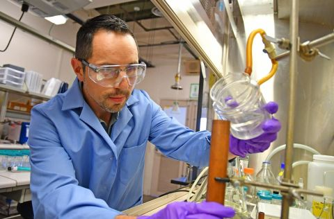 Explosives chemist David Chavez pours an example of melt-castable explosive into a copper mold at Los Alamos National Laboratory's Technical Area 9.