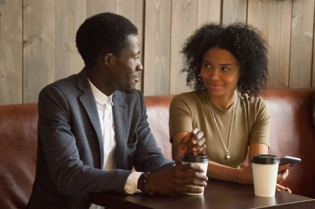 African man and woman talking flirting sitting at coffeehouse table