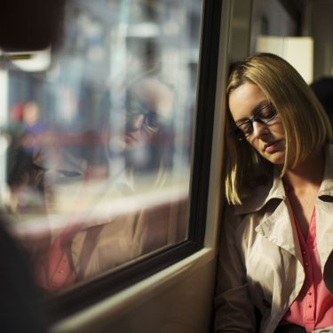 Businesswoman napping on train