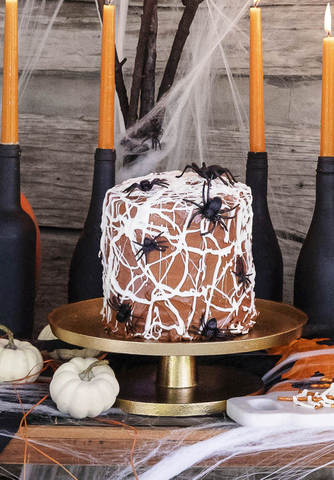 chocolate cake with white chocolate spider web frosting and fake spiders