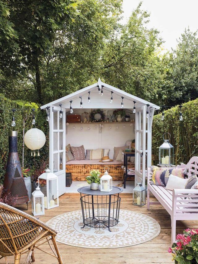 muebles de jardín caseta con guirnalda y sofá de madera