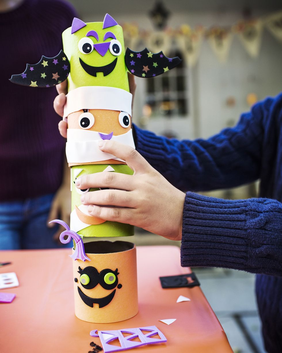 cropped image of boy stacking decoration at table during halloween party