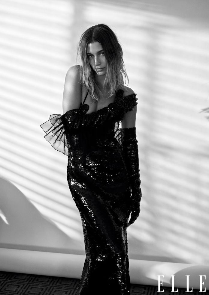 hailey bieber stands in front of a wall wearing a black sequined dress and matching evening gloves