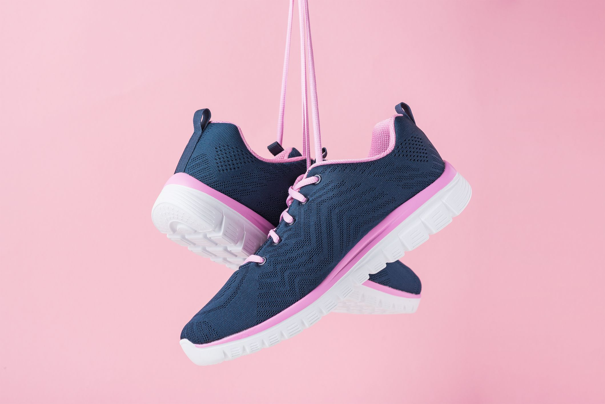 female sneakers for run on a pink background fashion stylish sport shoes, close up