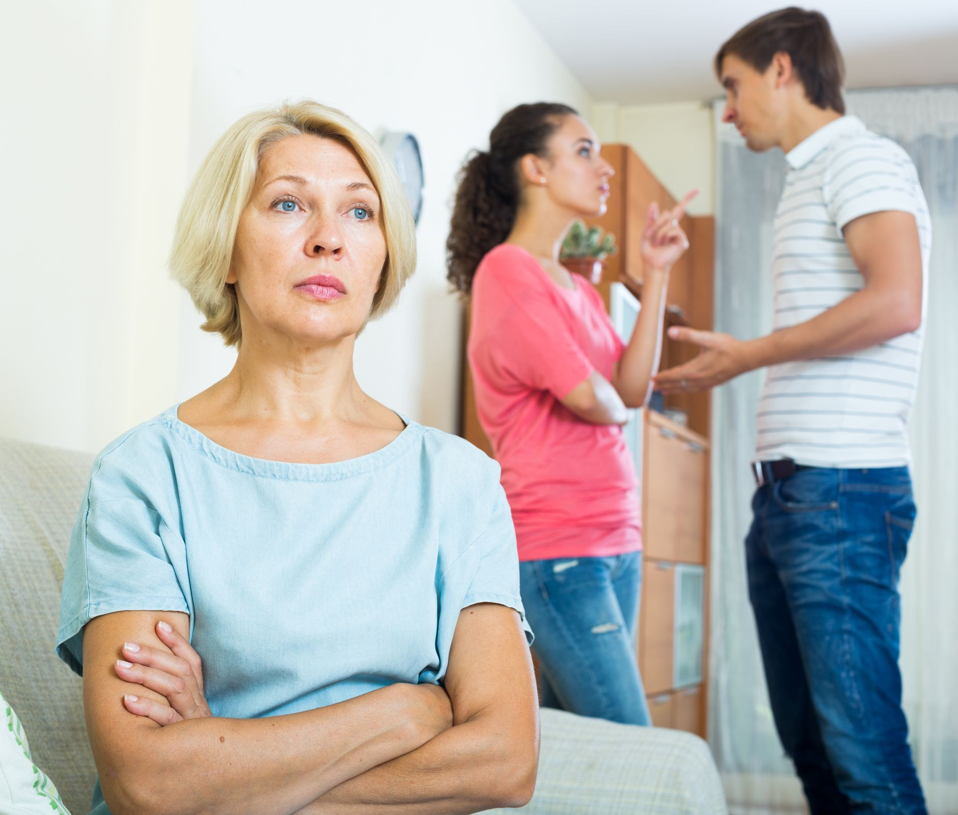 Mature woman watching young family couple quarrel at home