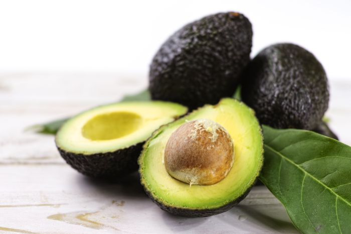 Green ripe avocado with leaves close up