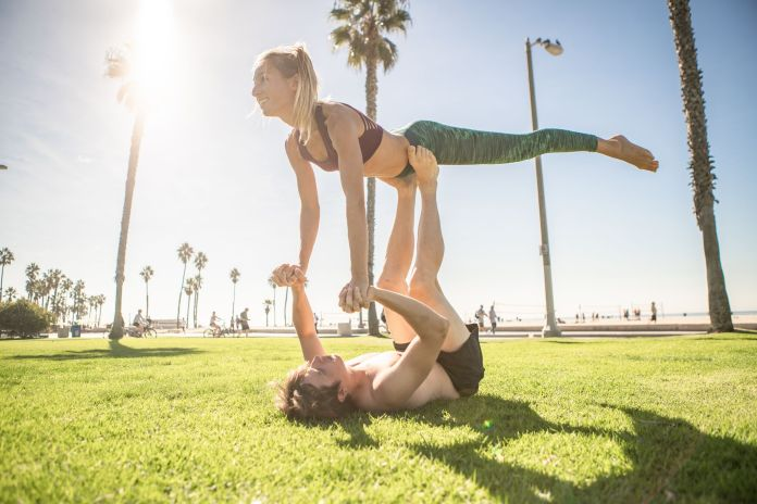 Joyful people practicing acroyoga outdoors