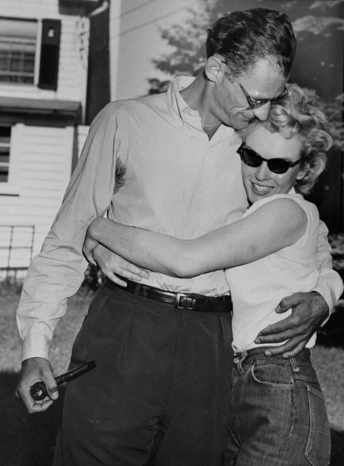 Marilyn Monroe hugs her fiance, Arthur Miller, on the lawn o