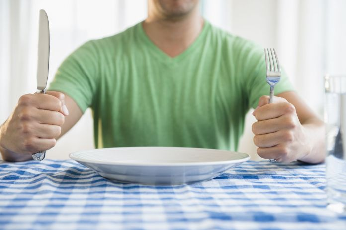 Mixed race man holding fork and knife at table