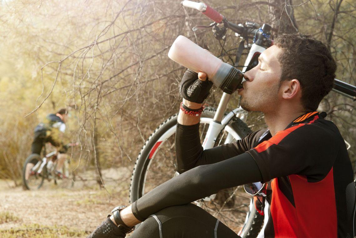 Mountain biker enjoying a beverage during his rest