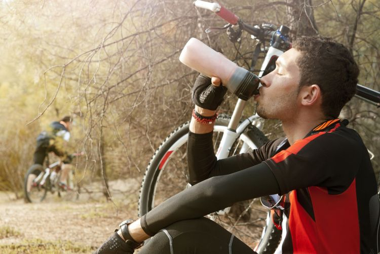 Mountain biker enjoying a beverage during his rest