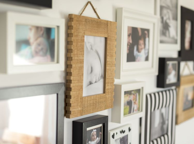 family in various photo frames on wall