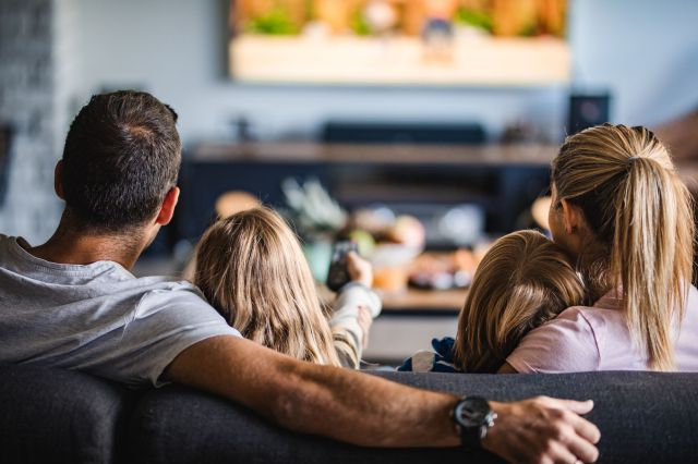 rear view of a family watching tv on sofa at home