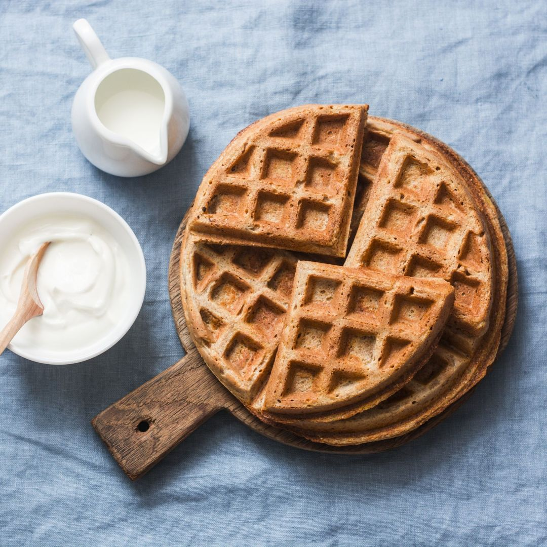 Savory gluten free breakfast waffles on a blue background, top view. Vegetarian food concept