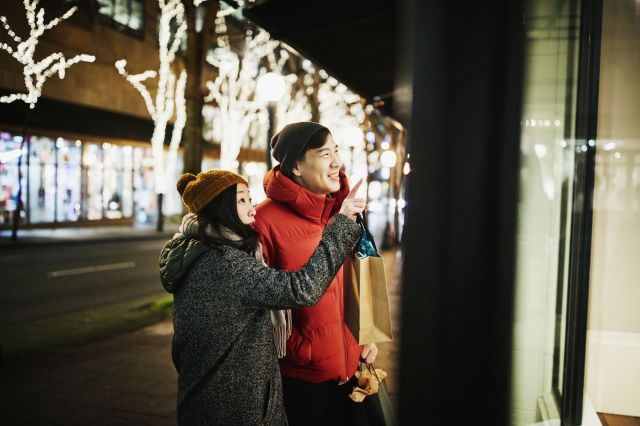 Smiling couple admiring items in widow while holiday shopping on winter evening
