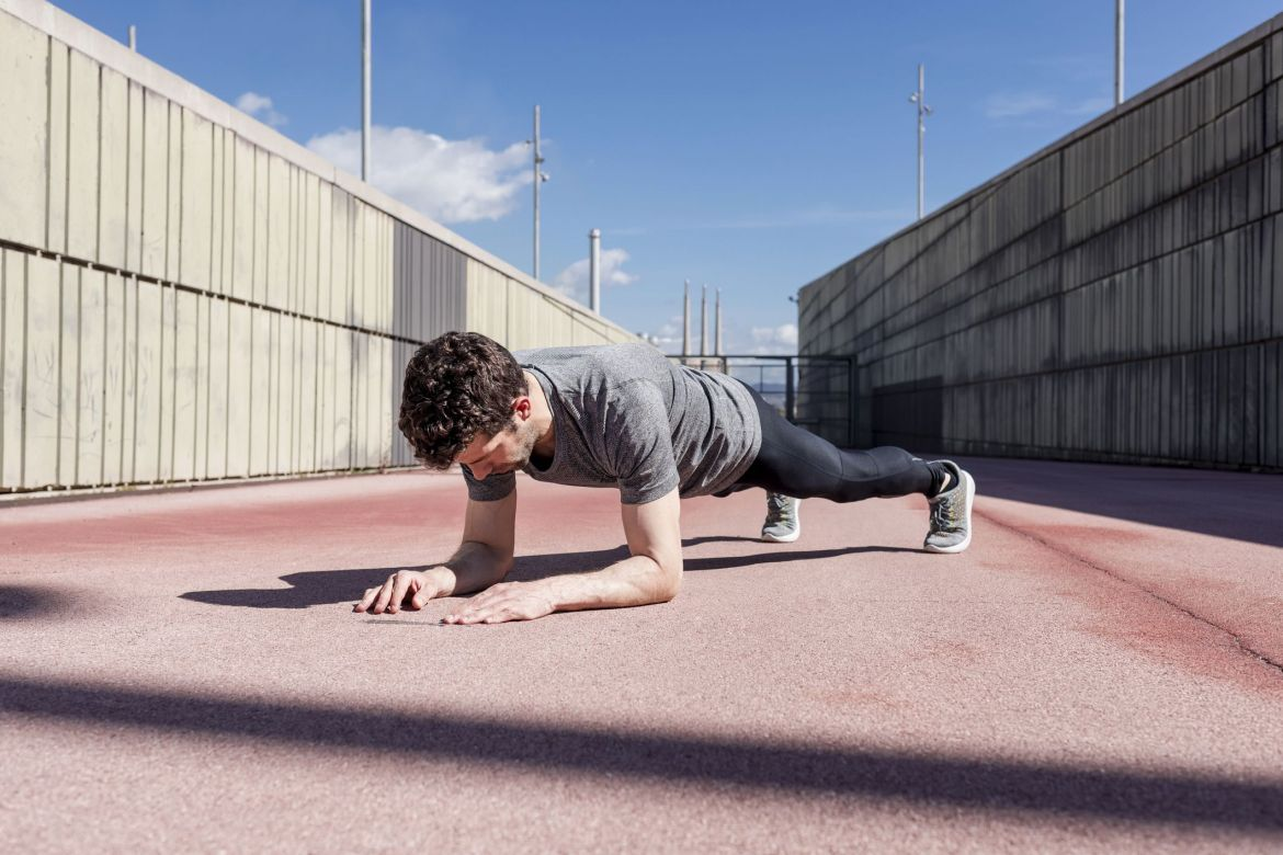 Sportive man exercising outdoors between walls