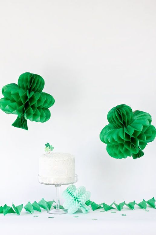 two green paper honeycomb shamrocks hanging above a white cake decorated with a green clover topper
