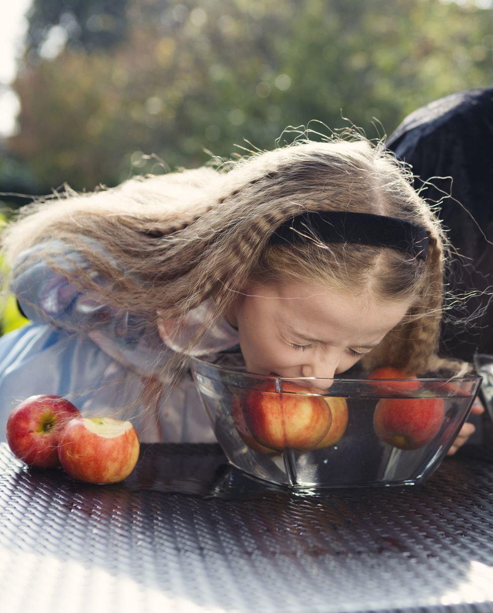two older children playing halloween bobbing for apples game