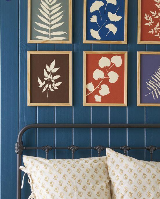 một lưới thực vật đầy màu sắc như bản in treo trên giường trong khung gỗ