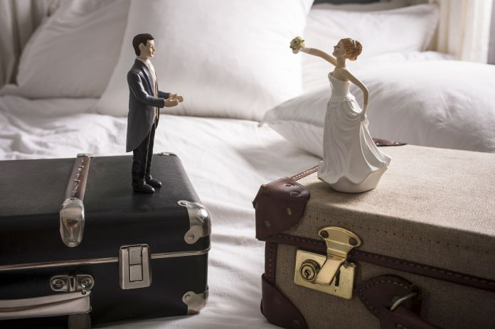 Wedding figurines on separate suitcases